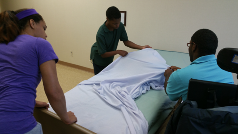 Three people making a bed
